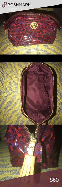 Tory Burch Burgundy Leopard Makeup Bag with Tassle Burgundy/purple leopard make up bag by Tory Burch. Tassel accent zipper pull. Expands to be very large. Small pocket inside. Gold Tory Burch logo centered in the middle of the makeup bag. New, never used. Tory Burch Bags Cosmetic Bags & Cases