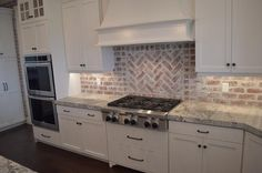 Lovely kitchen features a white wood French range hood situated over a red brick herringbone cooktop backsplash and an integrated gas cooktop over pot and pan drawers next to double ovens.