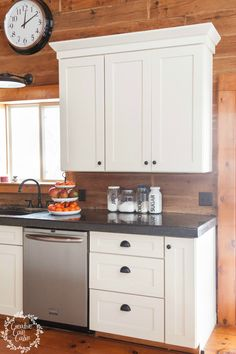 Black hardware on white cabinets creates the perfect contrast in this handsome cabin's kitchen. This is a look that's easy to achieve in your own home.