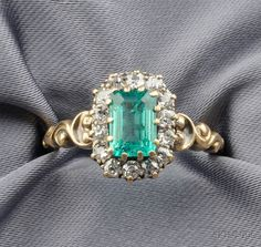Antique Emerald and Diamond Ring, prong-set with an emerald-cut emerald measuring approx. 7.15 x 5.45 x 3.00 mm, framed by old mine-cut diamond melee, scrolling shoulders, gold mount. [Best guess is late Georgian/Early Victorian]