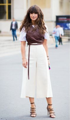Miroslava Duma wears a white t-shirt, leather vest, culottes, and strappy heels