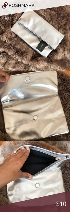 Forever 21 Metallic Silver Clutch NWT Silver Metallic Clutch from Forever 21. Purchased for an event but never used because it didn't match my dress. Black lining inside and fold over design. Forever 21 Bags Clutches & Wristlets
