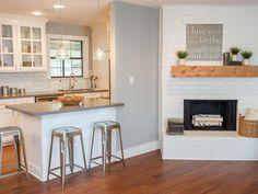 After removing half of the wall to the kitchen and updating the fireplace the living room has a welcoming, open feel. Angela can now cook and entertain without disappearing behind kitchen walls as seen on Fixer Upper.