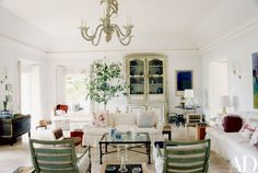 Bunny Mellon | Muted colors, painted furniture, skirted slipcovers, and a Diego Giacometti cocktail table furnish the tray-ceilinged living room; the framed museum poster on the far wall depicts a Mark Rothko painting | White, green.