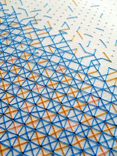 Geometric cross stitch A4 paper artwork in blue & yellow thread. Original abstract textile design by Rachel Parker.