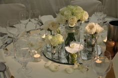 Beautiful mix of smaller floral clusters with mirrored round and votive candles.
