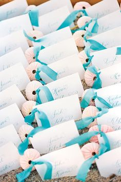 Beachy escort cards trimmed with ribbons and shells.