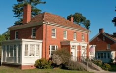 A two storey red brick home with a red tile roof and a white wooden framed sun room on each side.