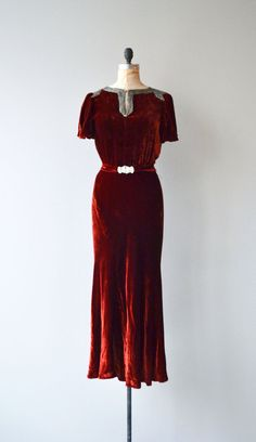 Vintage 1930s deep ruby red bias cut silk velvet gown with silver heavily beaded neckline and partial shoulders, subtle puff shoulder sleeves, matching belt with jeweled buckle and lovely slightly fluted skirt. --- M E A S U R E M E N T S ---  fits like: medium/large shoulder: 15 bust: 34-35 waist: 27-32 hip: up to 44 length: 55 brand/maker: n/a condition: some slight damage to the velvet at the back of the skirt, no holes, just some flattening/rubbing of the velvet.  ✩ la...