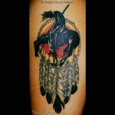 This beautiful illustration depicts a wounded Indian atop a horse, inked entirely in black. In contrast, the background is a dreamcatcher with a bright yellow and red interior. Several black and white feathers hang from the bottom.   #tattoos #tattoofriday #tattooart #tattoodesign #man'stattooidea #man'stattoos #dreamcatchertattoos #dreamcatchertattoosidea