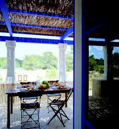 Porche tradicional con vigas en azul contrastando con el blanco de los muros y pilares. Las sillas ligeras en madera y hierro.