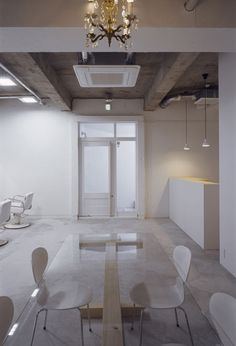 Japanese architect Makoto Yamaguchi has created a hair salon in the basement of a Tokyo building, showcasing the patchwork of alterations made by previous occupants of the space. Called kilico., the project involved patching the floor to make it flat and coating the various textures of the walls with white paint. White furniture, lighting and