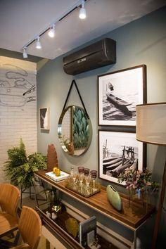 Esse é um cantinho de sala de jantar descolado e elegante ao mesmo tempo, isso porque temos os elementos certos: quadros em preto e branco, um espelho redondo super estiloso, um aparador de madeira combinando com as cadeiras e bastante verde.