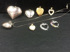 LARGE LOT OF HEART SHAPED PENDANTS INCLUDES THREE SILVER TONE PUFFY HEARTS (ONE WITH A 20 INCH CHAIN), AN ETCHED BRASS PUFFY HEART, TWO OPEN HEARTS WITH DAZZLING CRYSTALS, ONE SIGNED THAI AND ONE MARKED STERLING WITH A GOLD FINISH. ALL IN GREAT CONDITION