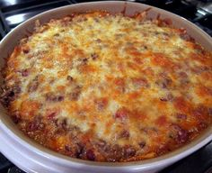 Ingredients: 1 pound lean ground beef 1 can Ranch Style beans 1 10-12 ounce bag tortilla chips, crushed 1 can Ro-tel tomatoes 1 small onion, chopped 2 cups shredded cheddar cheese, divided 1 package taco seasoning 1 can cream of chicken soup 1/2 cup
