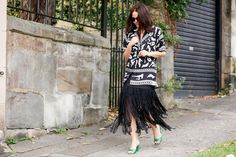A black chain fringe skirt is worn with a black and white printed jacket and green heels