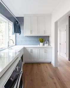 Amazing white laundry room renovation with grey blue tile backsplash. Modern laundry room, tons of space. Laundry Room Tile, White Laundry Rooms, Laundry Room Cabinets, Laundry Room Organization, Laundry Room Design, Kitchen Design, Kitchen Ideas, Laundry Room Island, Laundry Room Wallpaper
