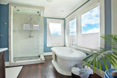 This master bathroom is gorgeous! Love the colors of the blue walls, white around the windows, and darker brown colored hardwood. It creates a beautiful relaxing feel and is perfect for getting ready in! Beach Chic Decor, Ocean Home Decor, Ocean House, Clawfoot Bathtub, Bathroom, Design, Washroom, Full Bath
