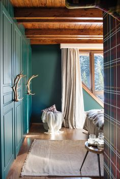 00447292b. Dormitorio rústico con paredes verdes y armario empotrado a juego con tiradores de asta_00447292b