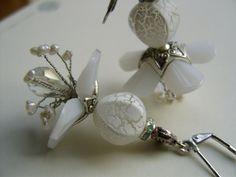 Ohrringe mit versilberten Schmuckelementen, die sich vorsichtig auf den zarten üppingen Blüten in weiß niedergelassen haben.   Transparenz in mattem w