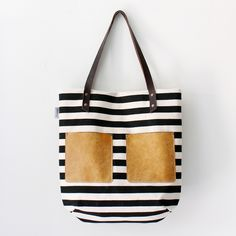 "A roomy carryall tote bag with two leather patch pockets on the front.  Perfect tote to the beach, to school or work!  The simple stripe pattern can easily pair with any outfit!* Hand-silkscreen printed heavy weight cotton canvas.* 5-6 oz durable brown leather strap handles. * Leather patch pockets.* Fully lined with linen/cotton mix fabric. * 2 large inner pockets. * Bag size: 15"" width X 16"" height * Strap drop: 9""This bag is handmade in California. Actua..."