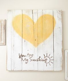 Sweet sentiment gets a dose of rustic style on this reclaimed wood piece, styled with a soft white wash and vibrant yellow hue to give the room an extra glow.