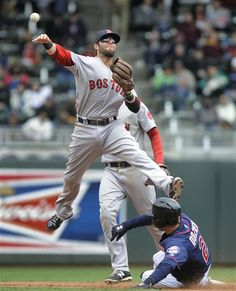 Dustin Pedroia sails over the Minnesota Twins' Brian Dozier after getting the force at second during the fourth inning in Minneapolis, Thursday, May 15, 2014.