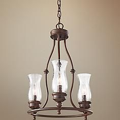 this three light mini chandelier comes in a beautiful heritage bronze finish with clear seeded glass hurricanes for an authentic antique look