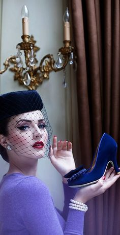 """Idda van Munster holding shoes from a line called """"Irregular Choice"""" -- the particular style is called """"Combi"""". And oh my, the luscious color of her sweater! Love veil length and angle."""