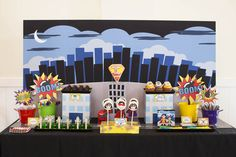 Superhero decor-- love the easy backdrop to the dessert table...would add yellow windows to the skyscrapers...like the pails and building risers for the food