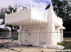 """Historic Pensacola, Inc. is restoring the Crystal Ice House, a drive-thru ice distribution house built in 1932.  It's now on the National Register of Historic Places. The exterior of the building and all the icicles are concrete. The paint is mixed with mica, so the whole building sparkles in the sun. On the front of the building, there's a slab illustrating the """"Hand Signals for Service,"""" i.e., how many fingers to hold up to indicate how much ice you wanted."""