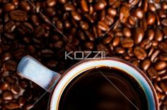 coffee cup and coffee beans - Coffee cup sits in a pile of coffee beans.