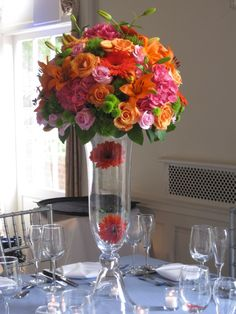 orange and hot pink and green flower taller style, not this vase and not with gerbera daisies, same flowers as the wedding but in a taller styling like this, but smaller in scale.