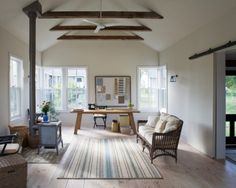 """Behind a sliding barn door is an alcove with a Murphy bed, enabling the studio to do double duty as a guesthouse. The ceiling beams are recycled, as well. """"There was an old barn on the  property, but it blew down around the time the clients bought it,"""" says  Schultz. """"They salvaged its exposed beams for the weaving studio."""" """"The same window, in the same size, is used everywhere but in the  bathroom because we wanted to keep a very controlled design vocabulary..."""