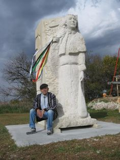 """Artist Jim Wahwassuck, who lives at the Prairie Band Potawatomi reservation near Mayetta, sits on the base of """"Tonantzin,"""" a 17-foot-tall sculpture of a Mascouten """"noble lady of state"""" he created to commemorate the 1830 Indian Removal Act, the forced relocation of Indians to lands east of the Mississippi River, and the Potawatomi Trail of Death, the forced removal of Potawatomi Indians from north-central Indiana to eastern Kansas in 1838."""