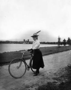 ~Bicycling in City Park, Denver~ Woman with a bicycle at City Park, Denver, Colorado, wears gloves, a locket, low-heeled shoes, and a hat with a flower and feather. A pavilion and lake are in the background. c.1900-20 Western History/Genealogy Dept., Denver Public Library.