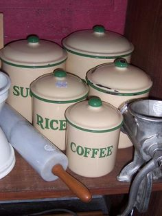 Five piece 1940's cream and green enamelware canister set, labelled for flour, sugar, rice, tea and coffee.