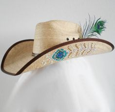Genuine Swarovski Rhinestones make up the peacock feather design on either side of this palm leaf cowboy hat. Rhinestones are attached with industrial strength glue which is weatherproof (just use cau