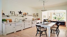 Perfection! Love the look and feel. Cream Country Kitchen with Barn Star and Industrial-style Pendant Lights. Open-plan space streamlined with a neutral scheme and white metro tiles along one wall. Think multi-use living area rather than kitchen.