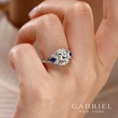 Gabriel NY - Preferred Fine Jewelry and Bridal Brand.  14k White Gold Round 3 Stones Halo Engagement Ring. Marquis cut sapphire side stones add a rich pop of color to this sumptuous engagement ring. An exceptional halo of pave diamond ribbons and a carved white gold band complete this elevated style. Find your nearest retailer->  https://www.gabrielny.com/storelocator