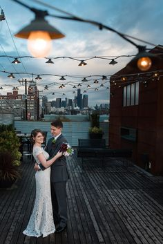 Sunset portrait of groom hugging bride with Seattle skyline in the background on the rooftop deck of wedding venue Within Sodo. Photographed by top Seattle wedding photographer Rebecca Ellison.  Within Sodo Seattle wedding venue