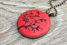 Pendant with black leaf and branch design. $38.00, via Etsy.