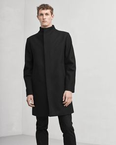 Sharp and minimalist straight fitted fully lined wool coat. Smartly tailored the coat has a smooth stand collar and concealed placket at front. <br> <br> - Warm and smooth Melton Wool <br> - Sharp stand collar <br> - Minimal detailing <br><br>  The