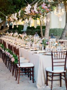 Modern, outdoor wedding reception decor idea -  hanging, greenery and floral chandelier with lantern and candle centerpieces {Destination Wedding Studio} #weddingreceptiondecorations #weddingcenterpieces #outdoorweddingreception
