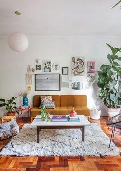 Sala de estar tem sofá bege escuro e parede galeria com quadros e objetos