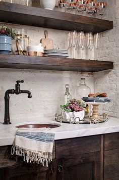 Filled with rustic charm, espresso stained shaker wet bar cabinets are topped with a white marble countertop finished with a hammered copper sink paired with a black vintage faucet.