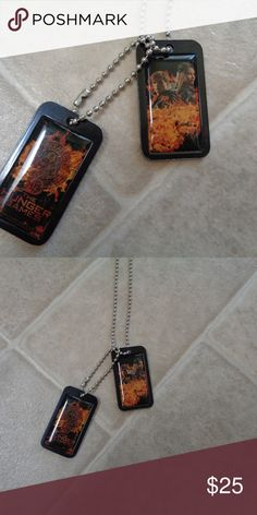 """The Hunger Games Katniss and Peeta necklace This necklace is a perfect gift for """"Everlark"""" shippers and fans of The Hunger Games. It features two attached dog tags, one with the District 12 logo and the other with Katniss and Peeta. I'm a crazy Hunger Games fan who was a little too merch-happy and need to let a few things go so I can work towards buying my first car and moving out! I'm 23, I need to get my life together. I love my fan merch, but I hardly wore this anyway and know there's a…"""