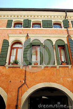 Photo taken in Oderzo in the province of Treviso in the Veneto region (Italy). In the picture you see the colorful facade of a building with the ground floor a big arch of the portico on the first floor and four windows with bow, three open and one closed with dark pale green. On the second floor you can see three more windows open and smaller.
