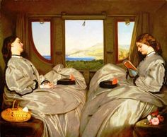 Two young women sat in a railway carriage. One has her eyes closed and the other is reading a book.