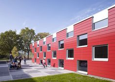 A chequerboard of opaque panels and windows surrounds thisschool canteen in western Germany